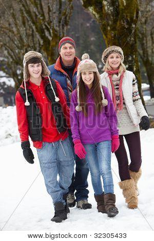 Teenage Family Walking Along Snowy Street In Ski Resort