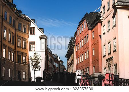Stockholm Narrow Street. Orange, Yellow Houses And Street Lights. View From Below Of A Cozy Narrow M