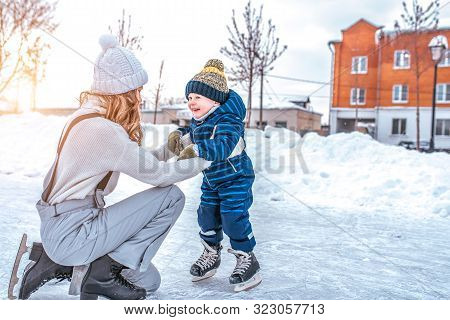 Mom With Baby Boy 3-5 Years Old, Learn To Train, Ride In Winter City On Rink, Ice Skating. Happy Smi