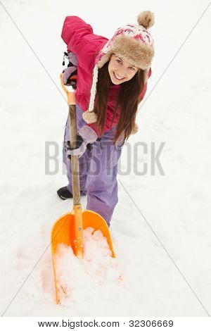 Teenage Girl Shovelling Snow From Path