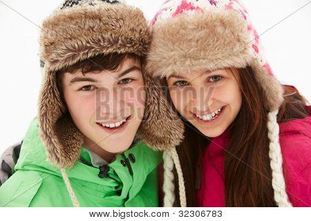 Portrait Of Teenage Couple In Snow Wearing Fur Hats