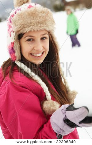 Teenage Couple Having Snowball Fight Wearing Fur Hats