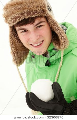 Teenage Boy Holding Snowball Wearing Fur Hat