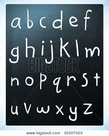 Complete English Alphabet Handwritten With White Chalk On A Blackboard