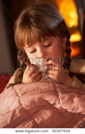 Sick Girl With Cold Resting On Sofa By Cosy Log Fire