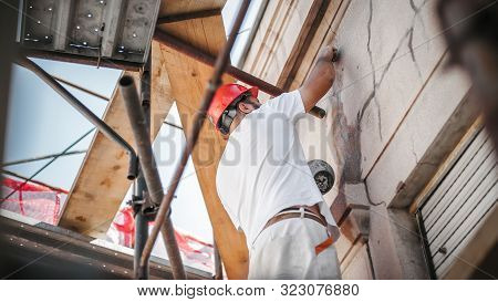 Man Worker Standing On Scaffolding And Restore Old Building Facade