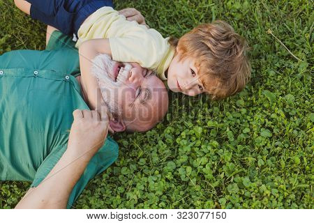 Hug On Green Grass - Grandfather And Grandson. Happy Senior Man Grandfather With Cute Little Boy Gra