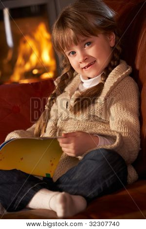 Young Girl Sitting On Sofa And Reading Book By Cosy Log Fire