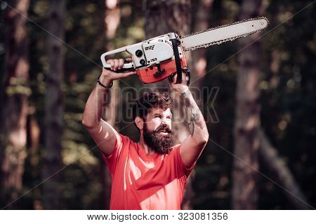 Stylish Young Man Posing Like Lumberjack. Lumberjack On Serious Face Carries Chainsaw. Lumberjack Wo