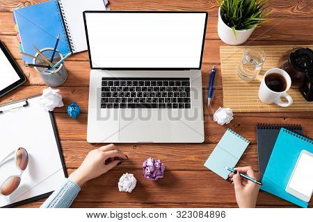 Top View Modern Office Workspace With Woman Hands. Flat Lay Wooden Desk With Laptop Keyboard, Cup Of