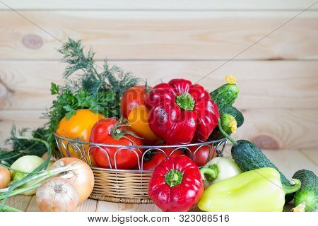 Vegetables Harvest In Wicker Basket On Wooden Background. Natural Organic Homegrown Products.