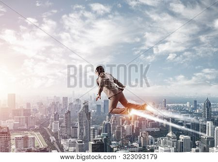 Businessman In Suit And Aviator Hat Flying In Blue Sky As Superhero. Business Person As Superman Wit