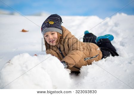 Boy Having Fun, Playing Outside, Surrounded With Snow. Wintertime, Healthy Kids Activity Concept