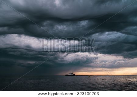 A Cargo Ship Underneath Stormy Clouds During Sunset