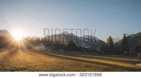 Winter Panorama In The Alps Mountains. Sunset Over Alpine Village On A December Evening, In Ehrwald,