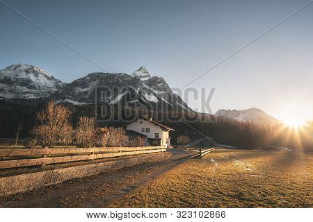 Snowy Alps Mountains Peaks And Austrian Farm In The Evening Light, On A Sunny Day Of Winter, In Ehrw