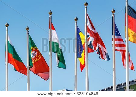 Flags Of Different Countries On The Flagpoles In Sunlight