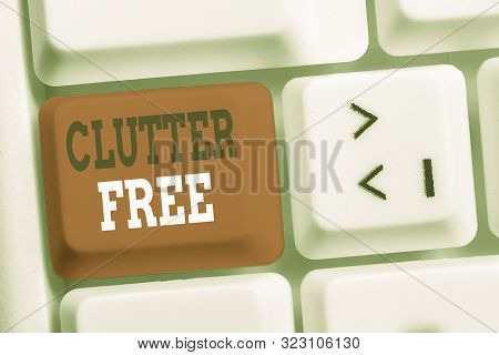 Handwriting text writing Clutter Free. Concept meaning Well organized and arranged Tidy All things in right places White pc keyboard with empty note paper above white background key copy space. poster