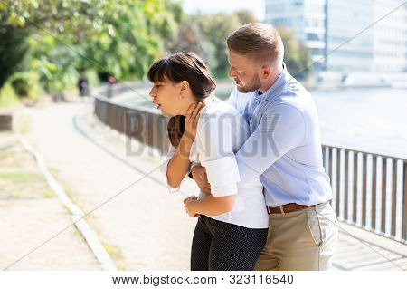 Man Helping Choking Woman To Expel A Trapped Object From Airway. Heimlich Maneuver