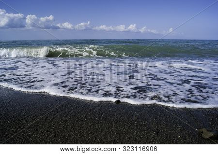 White Clouds Over Blue Rippling Sea With White Lamb Waves