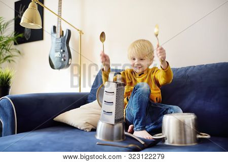 Mischievous preschooler boy play the music using kitchen tools and utensils. Funny drum part from little boy. Funny and developmental activity for creative kids at home poster