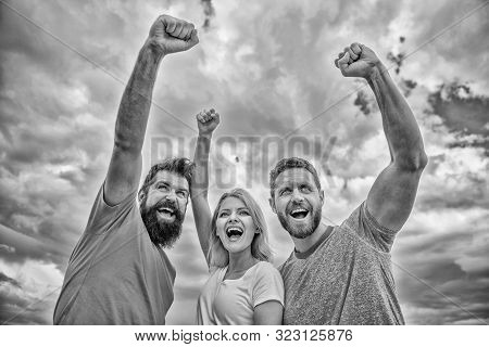 Yes we can. Woman and men look confident successful sky background. Behaviors of cohesive team. Celebrate success. Ways to build ohesive team. Threesome stand happy confidently with raised fists poster