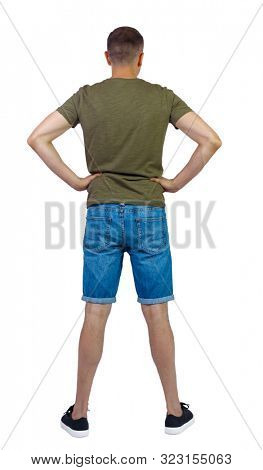 Back view of young manin shorts looking. Rear view people collection. backside view of person. Isolated over white background. A guy in shorts stands with his hands on his hips.
