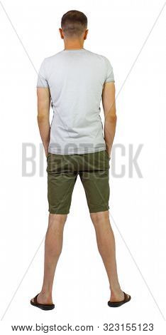 Back view of young manin shorts looking. Rear view people collection. backside view of person. Isolated over white bakground. A guy in shorts and slippers stands with his hands in the pockets
