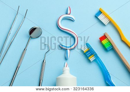 Dollar Sign Of Toothpaste. Tube Of Colored Toothpaste And A Toothbrush And Dentist Tools, A Mirror,