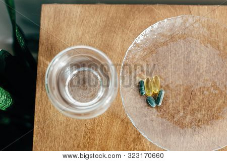 Omega 3, Spirulina, Chlorophyll Capsules And Glass Of Water On Wooden Table. Dietary Supplements, Bi