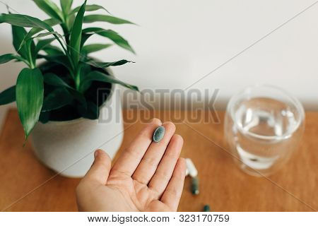 Dietary Supplements. Hand Holding Chlorophyll Tablet Above Glass Of Water On Wooden Table. Morning V