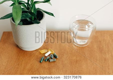 Omega 3, Spirulina, Chlorophyll,magnesium  Capsules And Glass Of Water On Wooden Table. Morning Vita