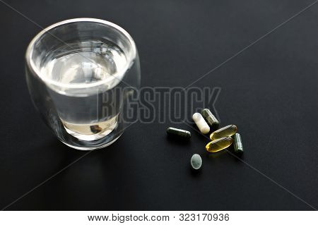 Dietary Supplements. Omega 3, Spirulina, Chlorophyll,magnesium  Capsules And Water Glass On Black Da