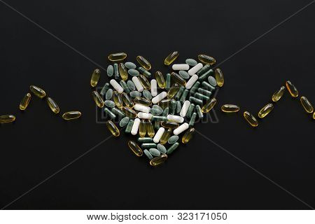 Health Support Concept. Omega 3, Spirulina, Chlorophyll, Magnesium Capsules In Heart Shape On Black