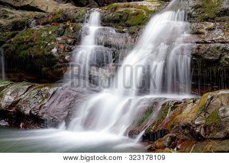 Waterfall In The Forest. A Waterfall Cascades Over Massive Stones. Cascading Waterfall Among The Sto