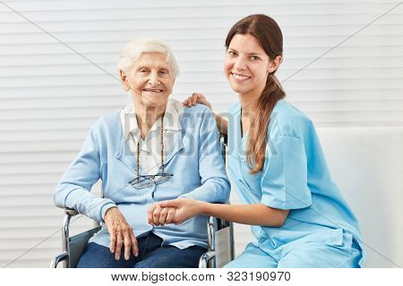 Caring caregiver and elderly woman in wheelchair at home nursing