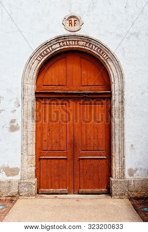 Loix-en-re, France - August 7, 2018: Beautiful Red Door In The Church Of The Village. The Words Libe