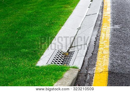 Drainage System Edge Tray With Concrete Grate For Rainwater Drainage Into The Sewer On A Road Side A