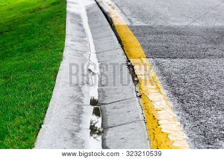 flowing rainwater in the canal is a cement ditch of a drainage system on the side of wet asphalt road with yellow markings and a green lawn on roadside. poster