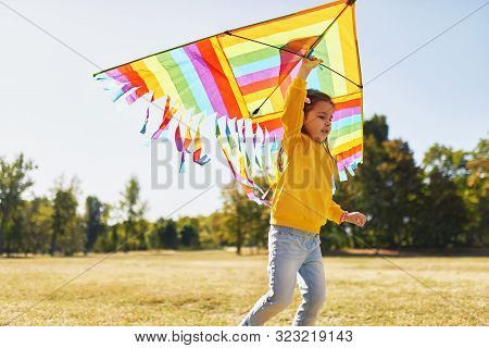 Image Of A Happy Child Little Girl Running With A Big Colorful Kite On A Sunny Day Outdoors. Cute Ki