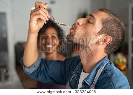 Man tasting spaghetti pasta while smiling woman look at him. Closeup face of young man tasting meal while cooking at home. Handsome guy eating noodles with fork in kitchen and feel his recipe.