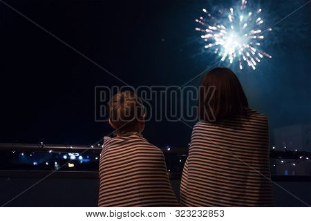 Mother And Son Looking At New Year Celebration Fireworks In Night Sky Warmly Wrapped In Striped Plai
