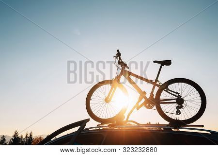 Mounted Mountain Bicycle Silhouette On The Car Roof With Evening Sun Light Rays Background. Safe Spo