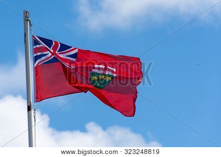 Red Ontario, Canada Flag Blowing In The Wind S On A Bright Sunny Day With Blue Sky.