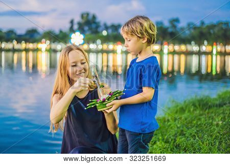 Mom And Son Tourists Holds The Loy Krathong In Her Hands And Is About To Launch It Into The Water. L
