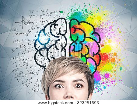 Head Of Astonished Blonde Young Woman Near Gray Wall With Colorful Brain Sketch With Formulas Drawn