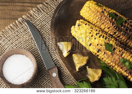 Delicious Grilled Mexican Corn With Parsley, Grilled Lemon And Salt. Top View Of Kitchen Table With