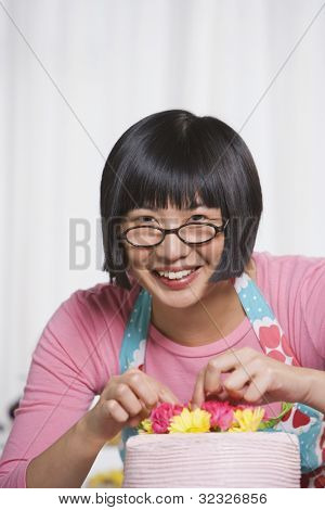 Young Asian woman putting flowers on cake