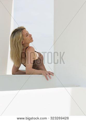 Beautiful Long Hair Blonde Woman In Brown Dress Enjoys Sunshine In White Window.