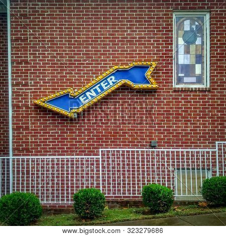 Vintage Style Arrow-shaped Enter Directional Sign And Stained Glass Window On Red Brick Wall Buildin